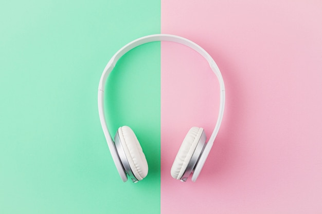 Minimal flat lay with wireless headphones over pink and light mint background.
