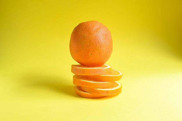 ミニマルフードコンセプトオレンジフルーツ明るい黄色の背景テキストトップビューミニマリズムクリエイティブフルーツのための空きスペース