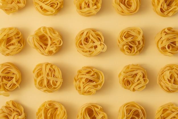 Минимальный образец пищи из макаронных тальятелле на светло-желтом пастельном фоне. закройте традиционные итальянские макароны в стиле поп-арт. паста, концепция итальянской кухни. вид сверху, плоская планировка