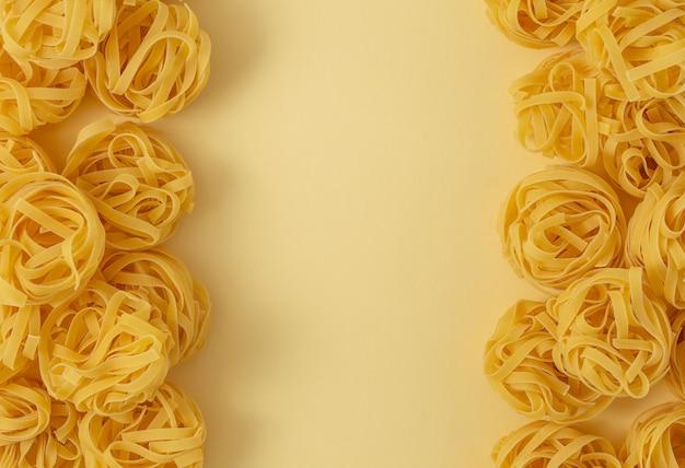 Минимальная еда шаблон тальятелле макаронных изделий, светло-желтый пастельный фон с пространством для текста. традиционная итальянская паста в стиле поп-арт, концепция итальянской кухни. вид сверху, плоская планировка, копия пространства