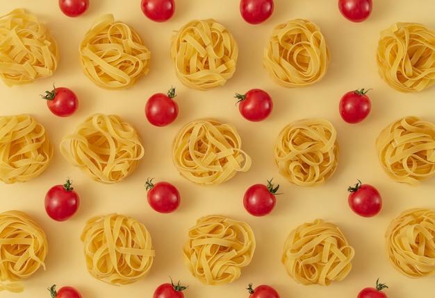 Минимальный образец пищи из тальятелле и помидоров, светло-желтый пастельный фон. традиционная итальянская паста в современном стиле поп-арт. паста и помидоры, концепция итальянской кухни. вид сверху, плоская планировка