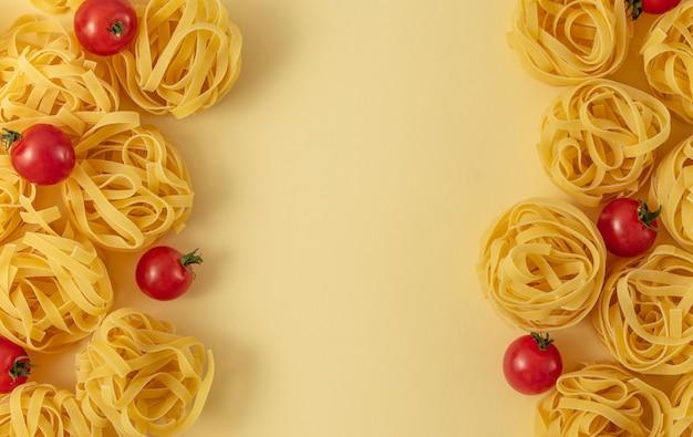 Минимальная еда шаблон тальятелле и помидоры, светло-желтый пастельный фон. традиционная итальянская паста в стиле поп-арт. паста и помидоры, концепция итальянской кухни. вид сверху, плоская планировка, копия пространства
