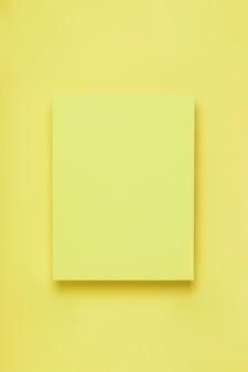 繊細なパステル調の背景に黄色い紙の最小限のフレーム。