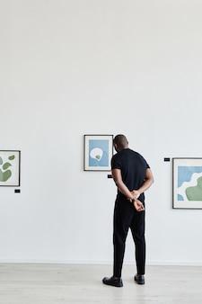 현대 미술 갤러리에서 그림을 보고 있는 아프리카계 미국인 남성의 최소 전체 길이 후면보기, 복사 공간