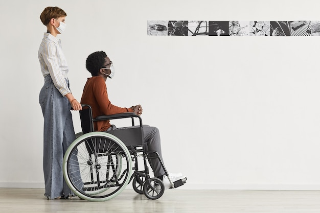 Minimal full length portrait of african-american man using wheelchair and looking at paintings in modern art gallery with young woman helping him, both wearing masks,