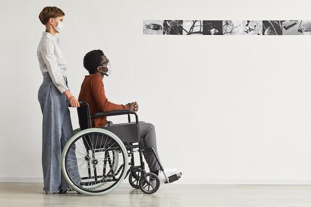車椅子を使用し、現代アートギャラリーで絵画を見ているアフリカ系アメリカ人の男性の最小限の全身像。若い女性が彼を助け、両方ともマスクを着用しています。