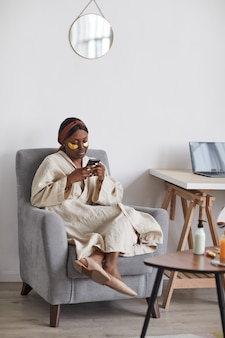 Minimal full length portrait of young african-american woman enjoying skincare routine at home and using smartphone, copy space
