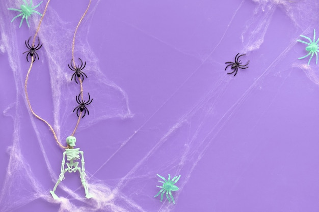 掛かったスケルトン、クモの巣、鮮やかな紫色のネオン紙に黒いクモのラインと最小限のハロウィーンの背景。トップビュー、トレンディな背景。