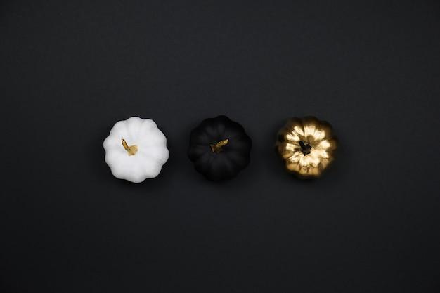最小限のハロウィーンの休日の概念。ハロウィーンの装飾、金色、黒と白のカボチャ、フラットレイ