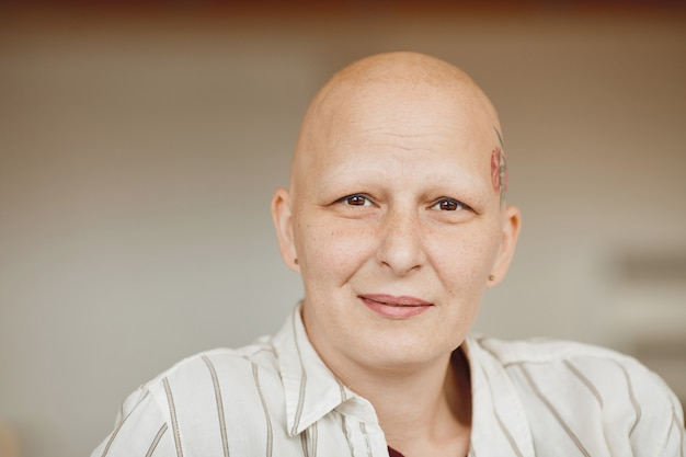 Minimal head and shoulders portrait of bald adult woman looking at camera and smiling while sitting on couch in warm-toned interior, alopecia and cancer awareness, copy space