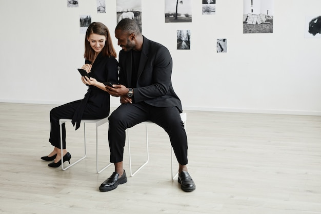 Minimal high angle portrait of elegant mixed-race couple wearing black while using smartphones in modern art gallery, copy space