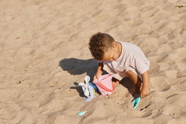 日光コピースペースのビーチで砂で遊ぶかわいい幼児の男の子の最小限の高角度の肖像画