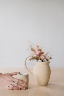 Минималистичный декор для дома с сухими цветами в керамической вазе и чашкой в женских руках