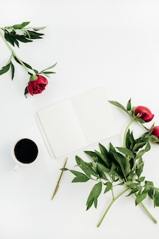 Minimal home office desk with blank notebook, coffee and peony flowers on white background. flat lay, top view