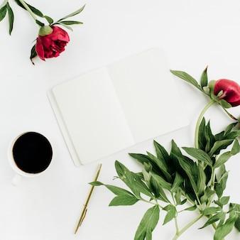 白い背景にノート、コーヒー、牡丹の花を持つ最小限のホーム オフィス デスク。フラットレイ、トップビュー