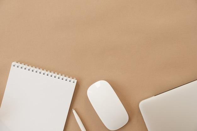베이지 색 배경에 최소한의 홈 오피스 데스크 작업 공간. 빈 시트 노트북, 노트북