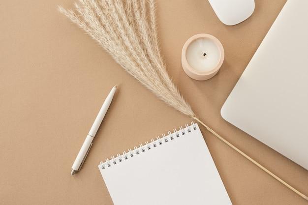 Minimal home office desk workspace on pastel beige. blank sheet notebook, laptop, pampas grass branch, decorations