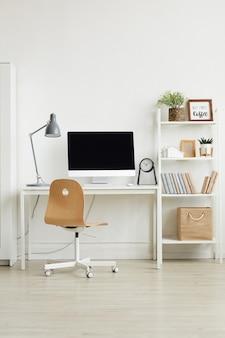 白い壁に木製の椅子と白いコンピュータデスクを備えた最小限のホームオフィスのインテリア