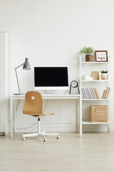 Minimal home office interior with wooden chair and white computer desk against white wall