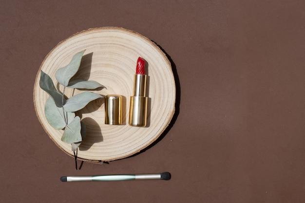 メイクアップブラシ、口紅、手のひらの影のオーバーレイを備えた最小限のモダンな化粧品シーン
