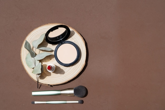 メイクブラシ、パウダー、ユーカリの葉を使った最小限のモダンなコスメティックシーン