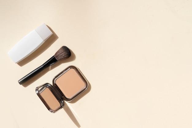 Минималистичная современная косметическая сцена с кистями для макияжа, пудрой, тональным кремом на нюдовом фоне