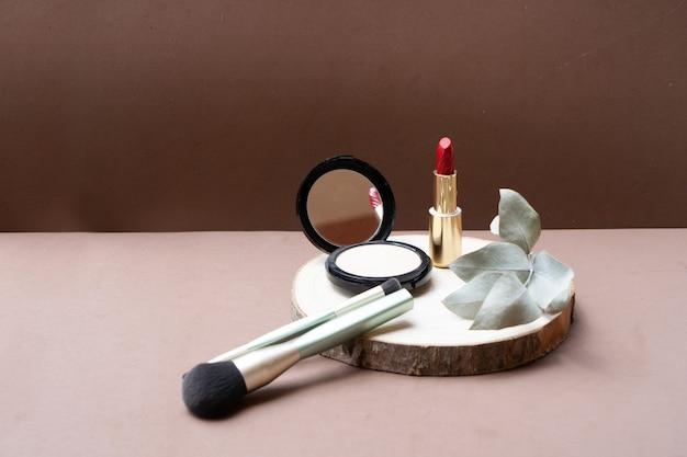 メイクアップブラシ、パウダー、口紅、ニュートラルベージュの背景を持つ最小限のモダンな化粧品シーン