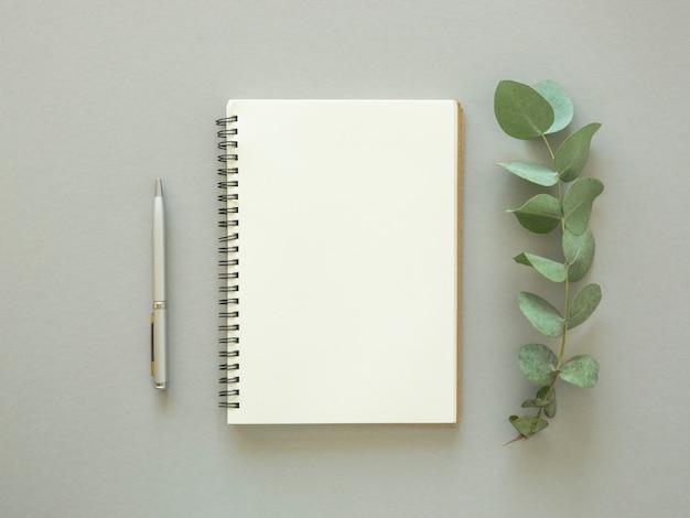 最小限のメモ帳シートのモックアップ。コピースペース、ペン、ユーカリの葉を持つ空のノートブック。上面図。