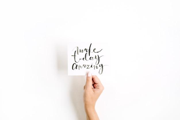 Минимальная бледная композиция с рукой девушки, держащей карточку с цитатой make today amazing, написанной в каллиграфическом стиле на бумаге на белой поверхности