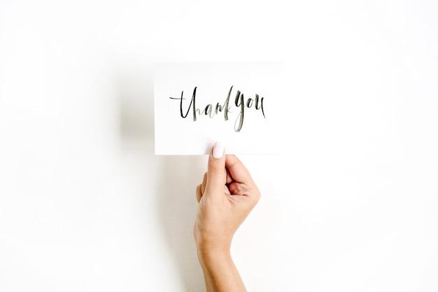 Минимальная бледная композиция с рукой девушки, держащей карточку с цитатой спасибо, написанное в каллиграфическом стиле на бумаге на белой поверхности