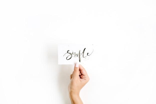 Минимальная бледная композиция с рукой девушки, держащей карточку со словом simple, написанным в каллиграфическом стиле на бумаге на белой поверхности