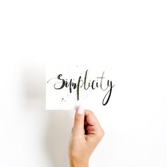 Минимальная бледная композиция с рукой девушки, держащей карточку со словом простота, написанным в каллиграфическом стиле на бумаге на белой поверхности