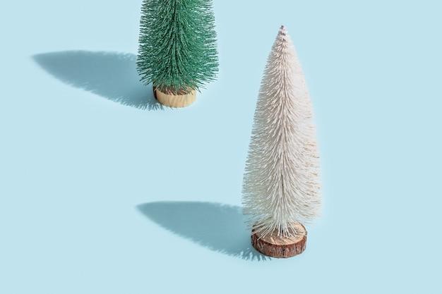 밝은 파란색 배경에 크리스마스 트리 녹색과 흰색 빛나는 색상이 있는 최소 패턴