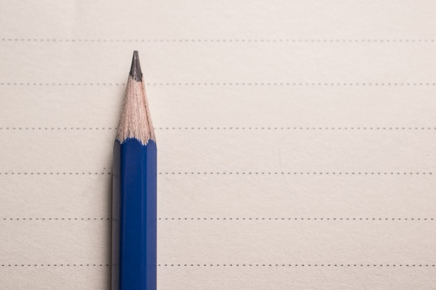 Minimal pencil on notebook lines background with copy spcae view from above.