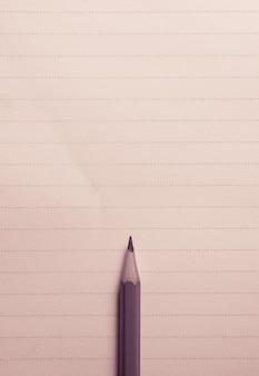Минимальный карандаш на тетради выравнивает предпосылку с взглядом spcae экземпляра сверху.