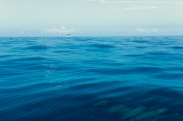 Minimal photography of fishery boat floating over blue sea wave