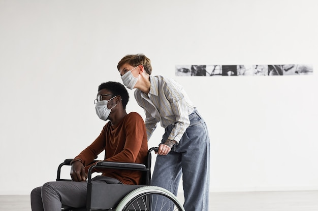 Minimal portrait of african-american man using wheelchair and looking at paintings in modern art gallery with young woman helping him, both wearing masks,