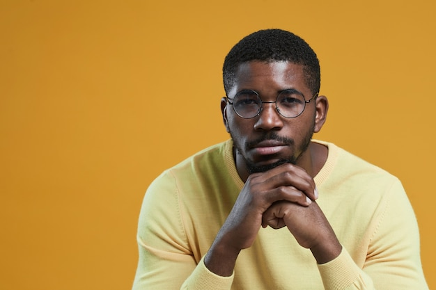 Minimal portrait of africanamerican man wearing glasses and looking at camera while resting chin on ...