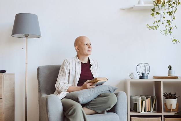 Minimal portrait of bald adult woman holding book and looking away pensively while sitting in comfy armchair at home, alopecia and cancer awareness, copy space