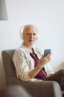 Minimal portrait of bald adult woman looking at camera while listening to music via smartphone at home, alopecia and cancer awareness, copy space