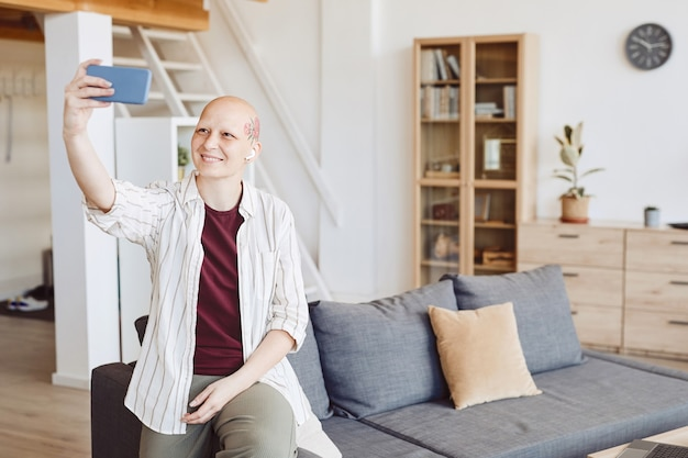 Minimal portrait of bald adult woman with head tattoo taking selfie and smiling happily while standing in modern home interior, alopecia and cancer awareness, copy space