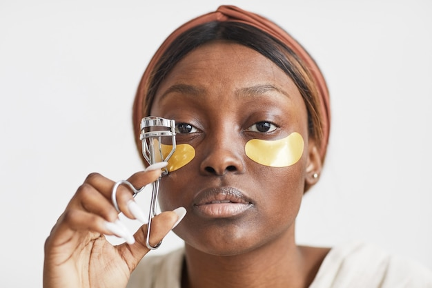 Minimal portrait of beautiful african-american woman enjoying skincare routine at home and curling eyelashes, copy space