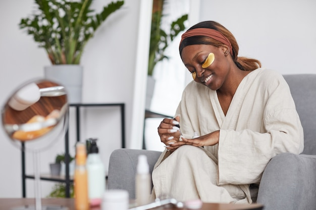 Minimal portrait of beautiful african-american woman enjoying skincare routine at home and doing manicure, copy space
