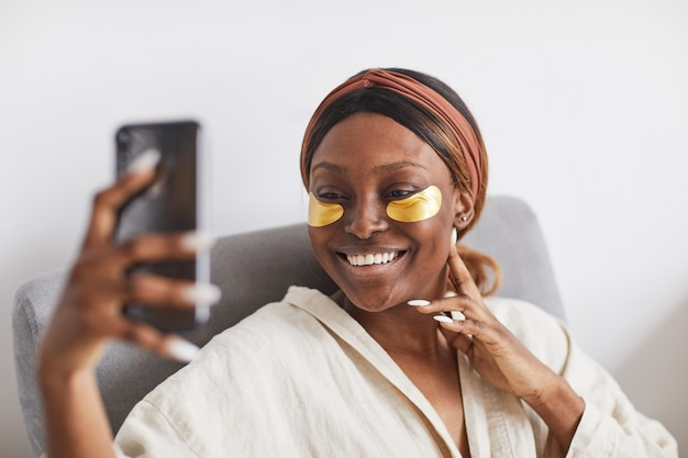 Minimal portrait of beautiful african-american woman enjoying skincare routine at home and speaking by video chat, copy space