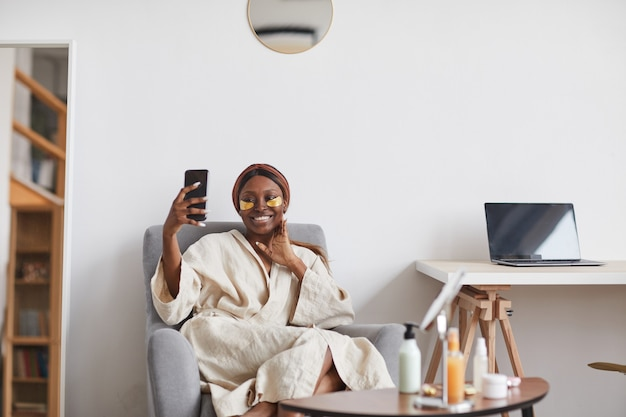 Minimal portrait of beautiful african-american woman enjoying skincare routine at home and taking selfie, copy space
