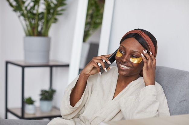Minimal portrait of beautiful african-american woman speaking by smartphone while enjoying skincare routine at home, copy space