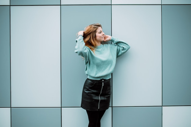 Minimal portrait of a beautiful young girl standing against blue wall