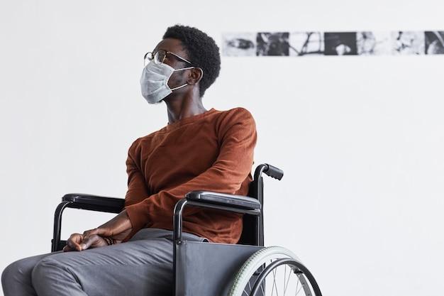 現代アートギャラリーで絵画を見ながら車椅子を使用し、マスクを着用しているアフリカ系アメリカ人の男性の最小限の肖像画、