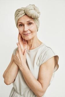 머리 스카프를 착용하고 흰색 배경에 대해 포즈를 취하는 아름다운 성숙한 여성의 최소한의 초상화