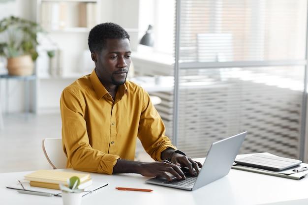 사무실에서 흰색 책상에 앉아있는 동안 노트북을 사용하는 현대 아프리카 계 미국인 남자의 최소 초상화, 복사 공간